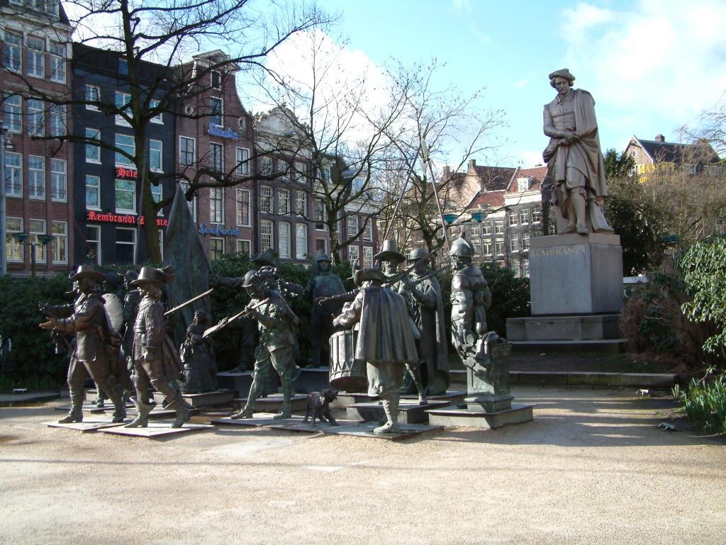 """Rembrandtplein - Auf dem ehemaligen Buttermarkt in Amsterdam steht eine Rembrandt Statue. Seit Rembrandts 400. Jahrestag 2006 bis 2009 befanden sich in der Mitte des Platzes vor dem Rembrandt-Denkmal mehrere kleinere Statuen, die das berühmte Gemälde Rembrandts """"Die Nachtwache"""" repräsentierten."""