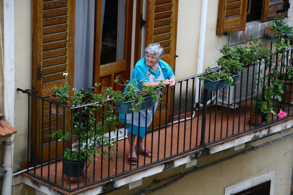 Alte Sizilianerin in blauer Schürze schaut kritisch vom Balkon runter