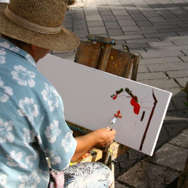 Straßen-Maler auf der Piazza IX Aprile zeichnet Bildern als Motiv den Uhrturm, den Torre dell'Orologio