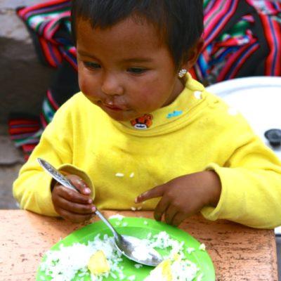 Peruanisches Kind ist Reis mit Gemüse