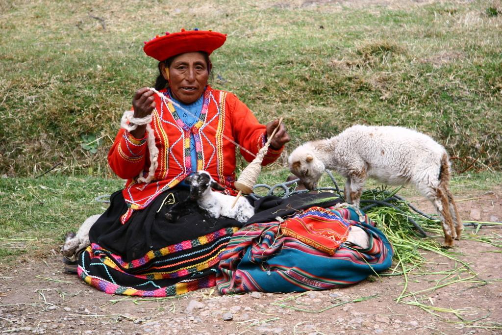 Traditionell gekleidete, peruanische Spinnerin mit Lämmchen