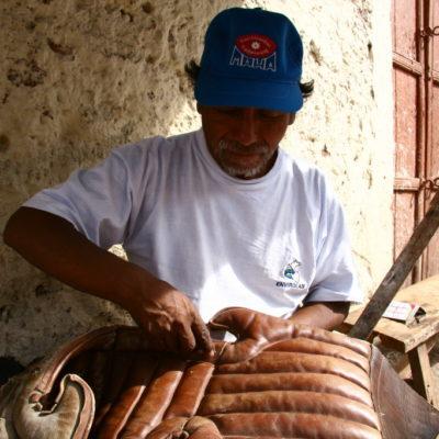 Altes Hadwerk - Ein Riemer repariert einen Sattel auf den Straßen von Cusco