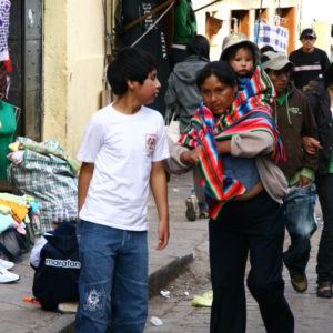 Auf den Straßen von Cuzco - Mutter trägt ihr Kind im peruanischen Tragetuch aus buntem Mantastoff