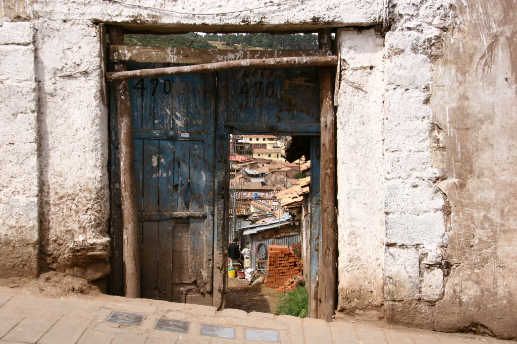 Blick durch alte Tür auf Innenhof und Dächer in Cusco
