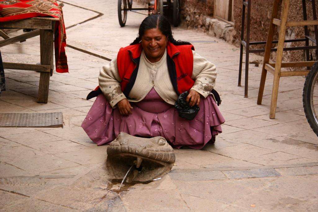 Cholita über einem Schlangenbrunnen in Písac / Peru