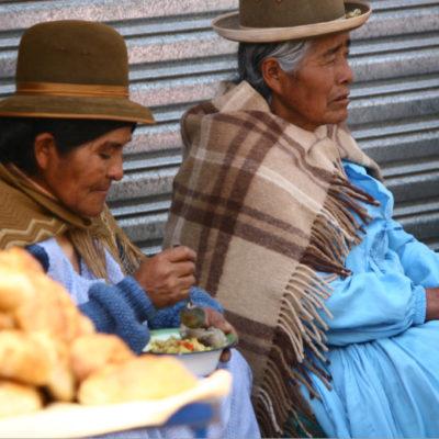 Cholitas auf der Straße beim Mittagessen
