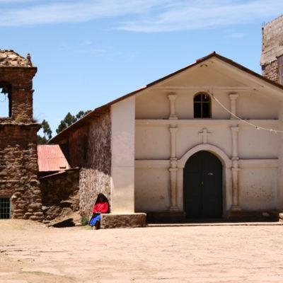 Eine Taquileña webt vor der alten Kirche von Taquile