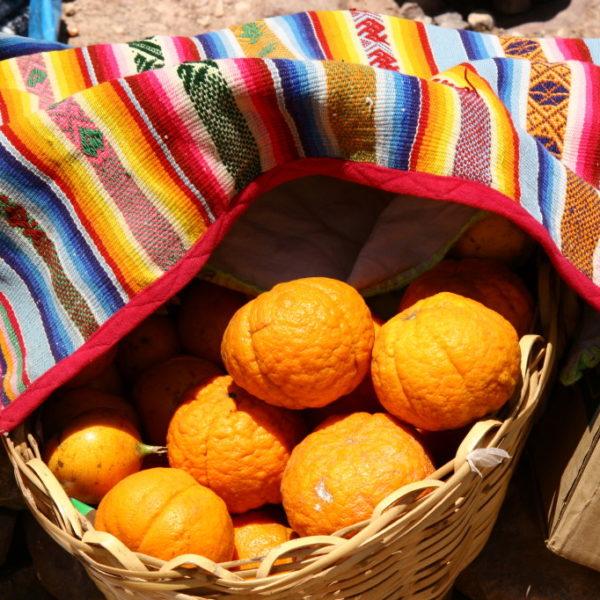 Frische Orangen unter buntem, peuanischen Tuch