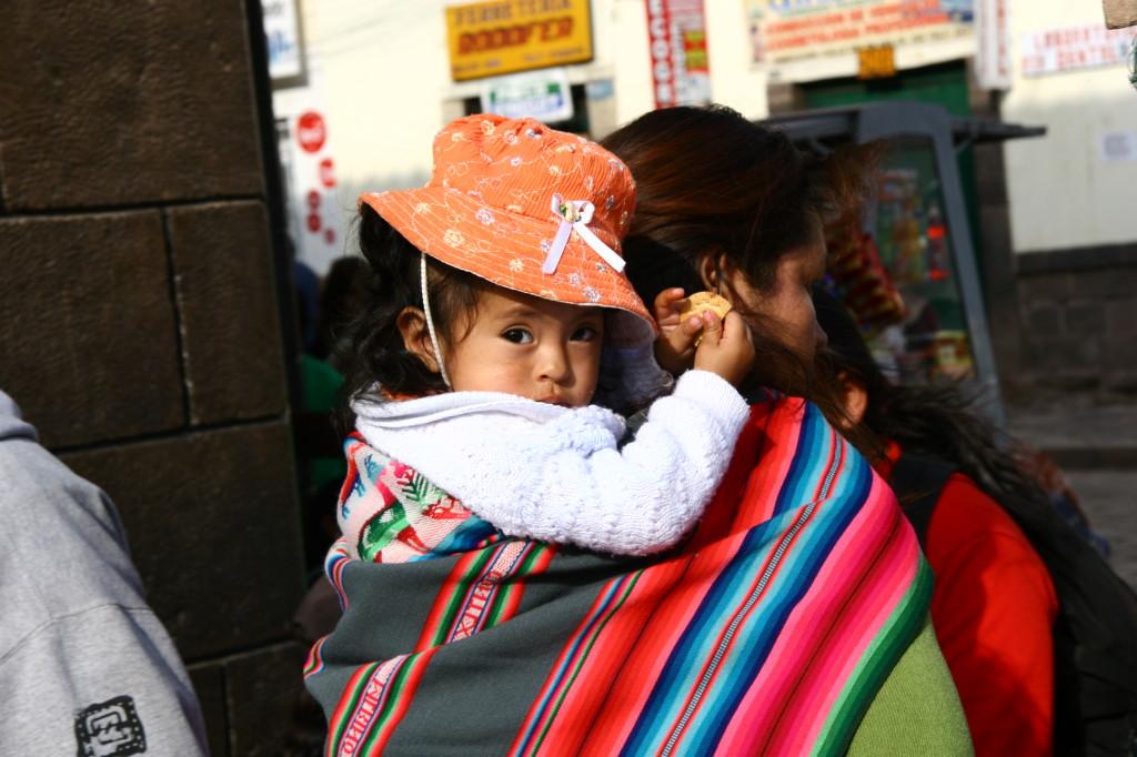 Kleines Mädchen im peruanischen Tragetuch aus buntem Mantastoff