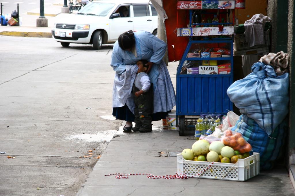 Peruanische Mama wischt ihrem Sohn den Mund mit ihrer Schürze ab