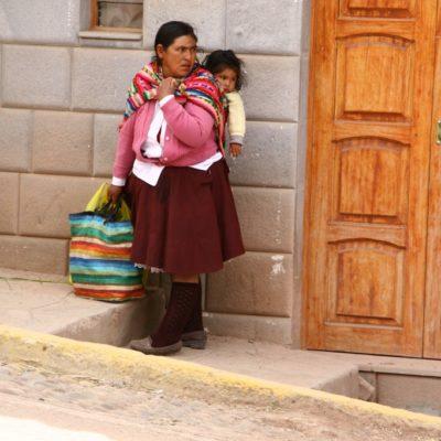 Peruanische Mutter mit Kind im Tragetuch in Chinchero