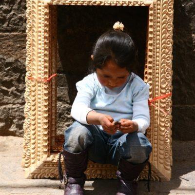 Schönes Bild - Kleines Mädchen sitzt in einem großen Bilderrahmen