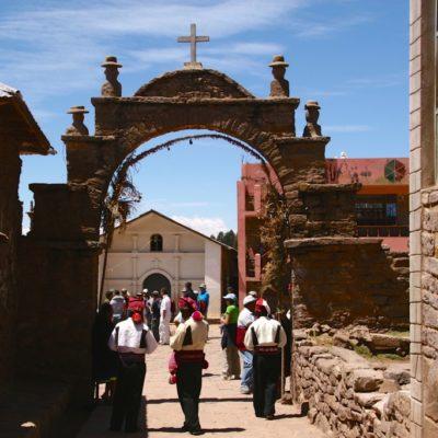 Strickende Männer vor dem Tor zum Dorfplatz auf der Insel Taquile