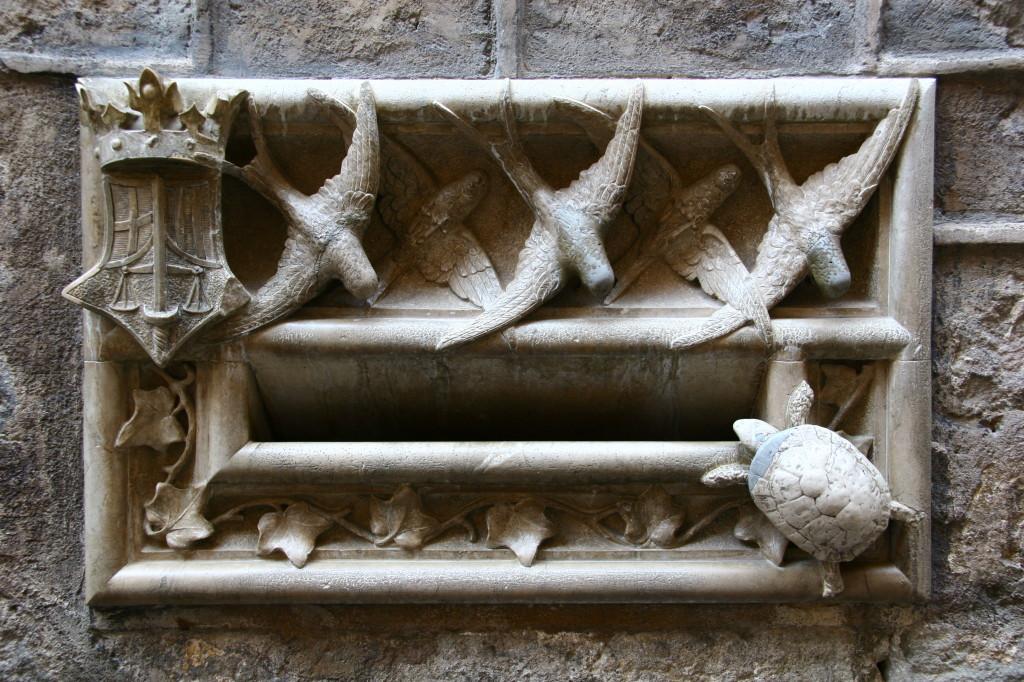 Marmorbriefkasten am Eingang des Carrer del Bisbe -  Die fliegenden Schwalben zeigen wie schnell die Justiz arbeiten sollte, die Schildkröte symbolisiert die Realität...