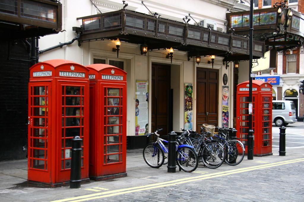 Rote Telefonzellen vor einem Pub