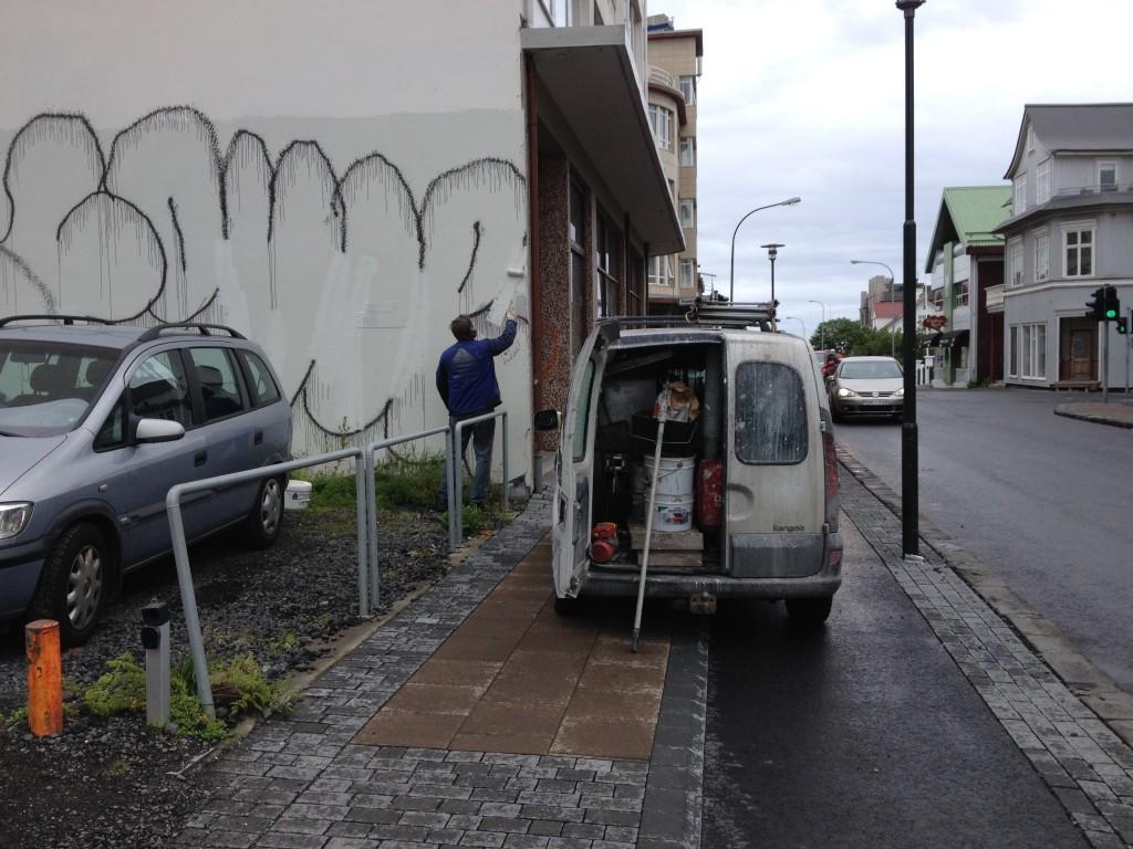 Schluss mit Schmierereien - Maler weißelt eine Hausfassade