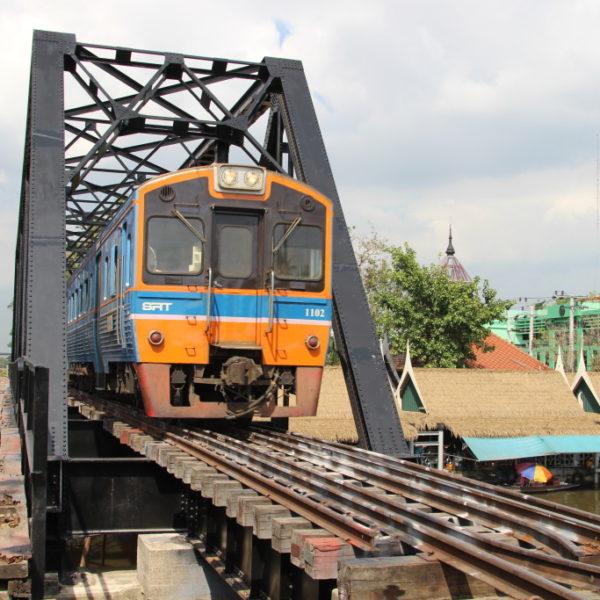 Der Zug fährt ein über den Geleisen über dem Wat Talingchan Floating Market