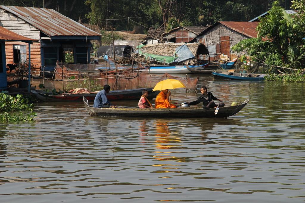 Ein Mönch fährt im Boot von Haus zu Haus und empfäng die Opfergaben auf dem Mekong
