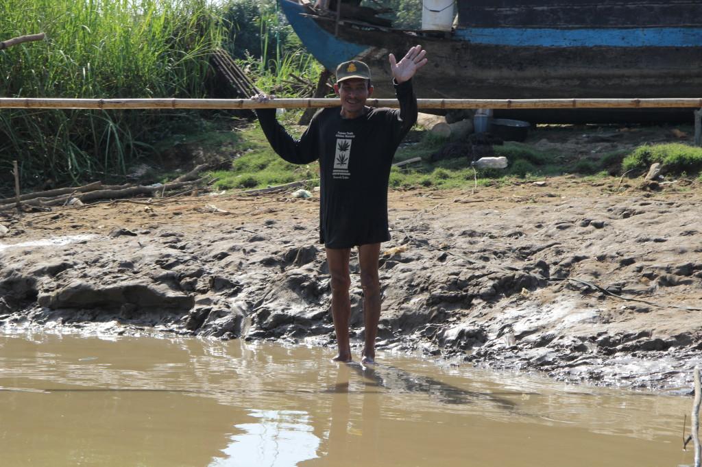 Freudlich winkt ein Mekong-Fischer dem Boot zu