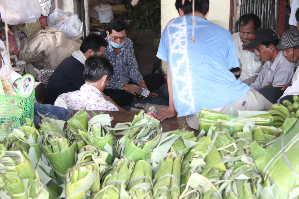 Kartenspieler hinter Bananenblättern