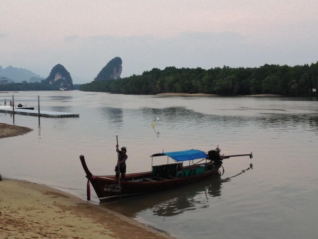 Ein Fischer legt vor den bizarren Felsen Khao Kanab Nam in der Andamensee an.