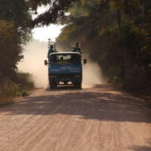 Ein kleiner Laster wirbelt auf der Straße nahe Battambang viel Staub auf.