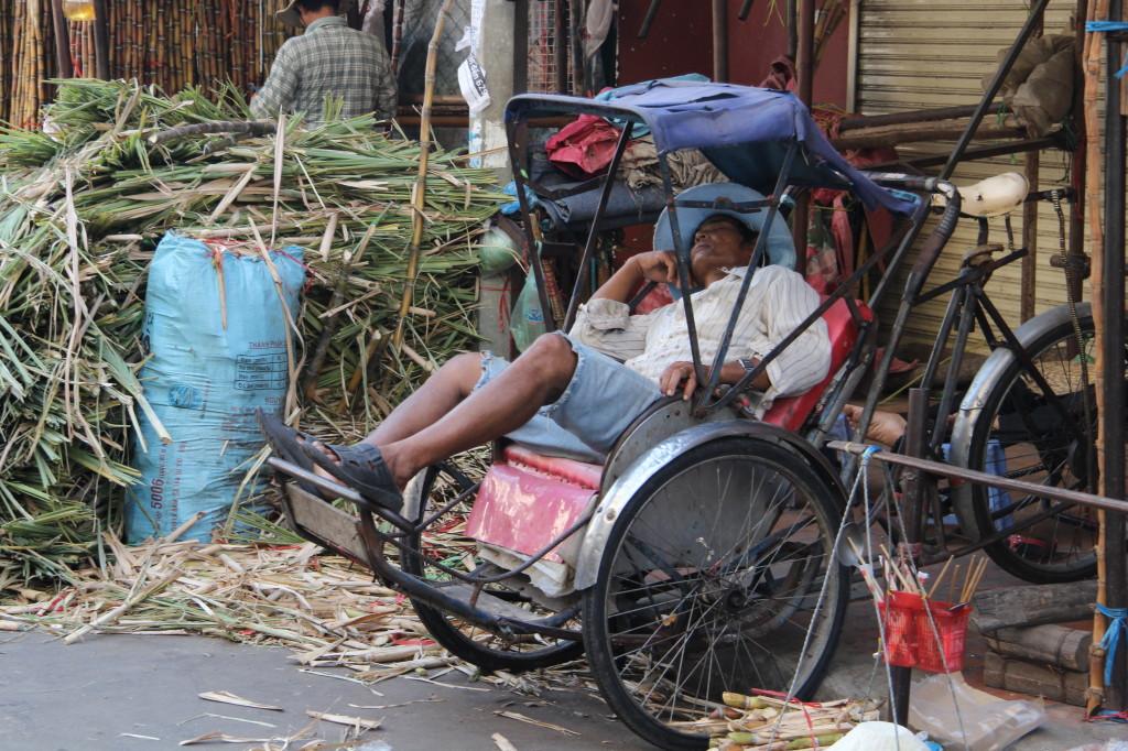 Schlafender Rikscha-Fahrer: Auch wenn es in Phnom Penh wuselg zugeht, kommen Einheimische an den belebten Staßen zur Ruhe.