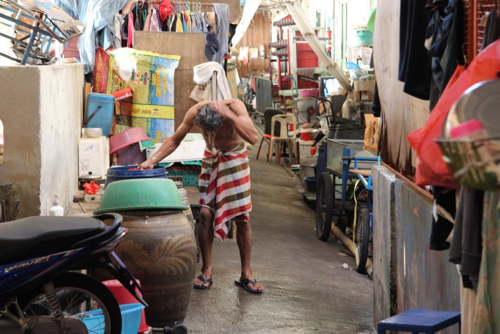 Schnelle Dusche in einer Gasse des Tha Tian Market