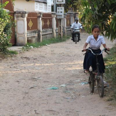 Schulmädchen in Uniform auf dem Fahrrad