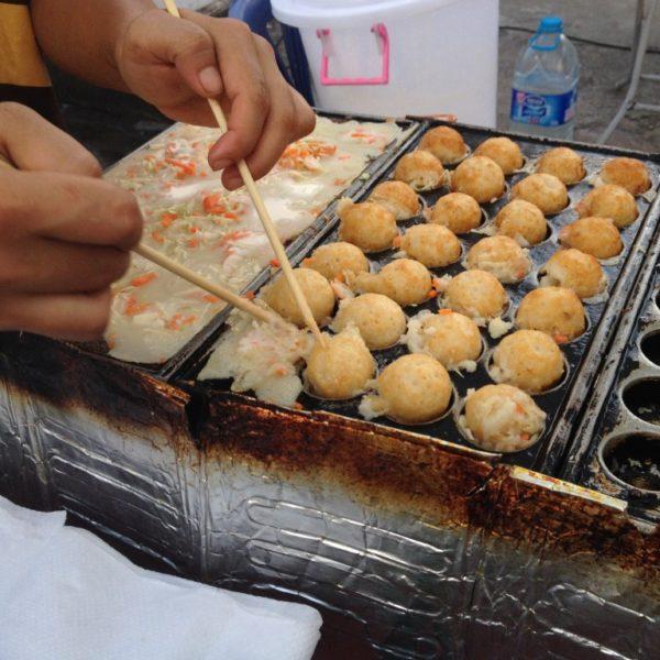 Straßenfest in Krabi - Mit Stäbchen und viel Geschick werden kleine Tintenfisch-Teigbällchen vorbereitet.