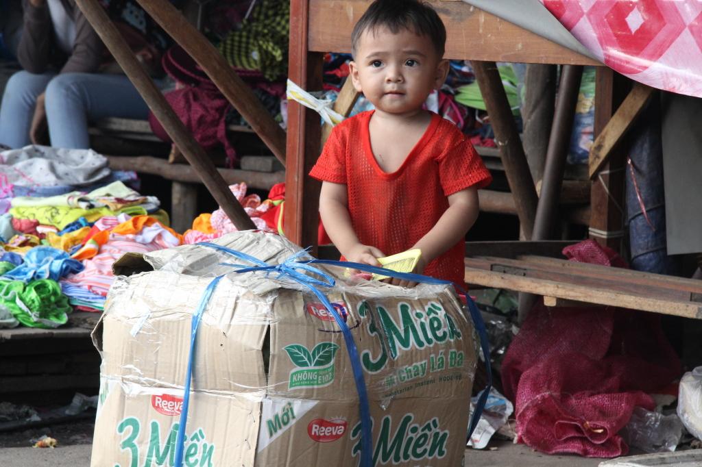 Versteckspiele hinter großen Paketen auf dem Markt in Sihanoukville