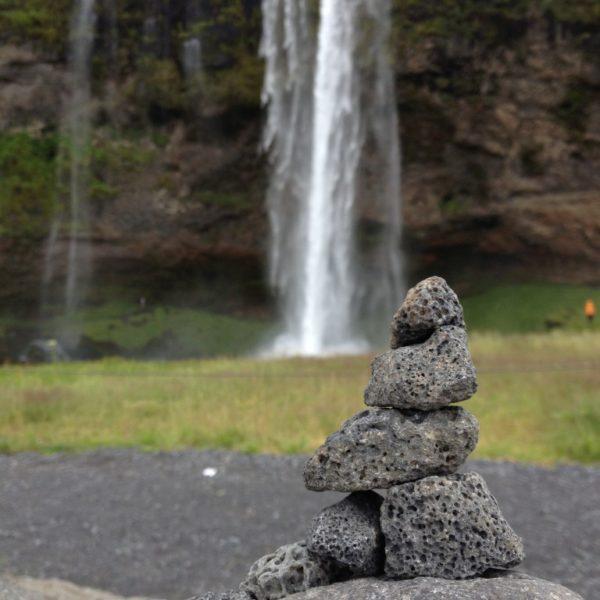 Steintuürmchen vor dem Wasserfall Seljalandsfoss
