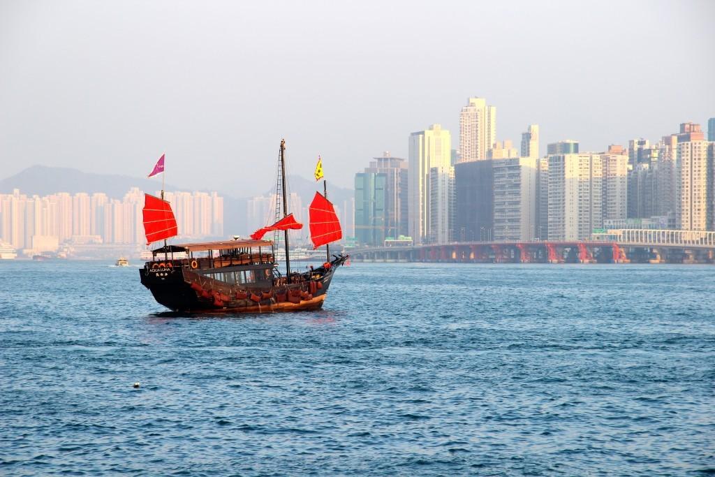 Dschunke mit roten Segeln vor der Skyline von Hongkong