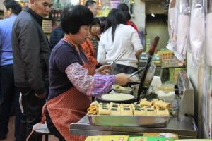 Ein küstlicher Duft der frisch gefertigten Waffelröllchen verführt die Passanten zum Kauf
