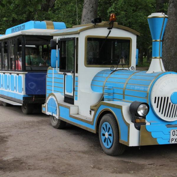 Ein blauer Zug im Schlosspark Peterhof fährt müde Besucher durch die weitläufigen Anlagen