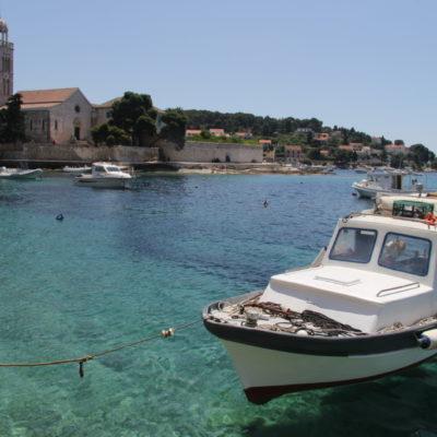 Kleine Boote schweben auf dem kristallklaren Wasser vor dem Franziskaner-Kloster in Hvar